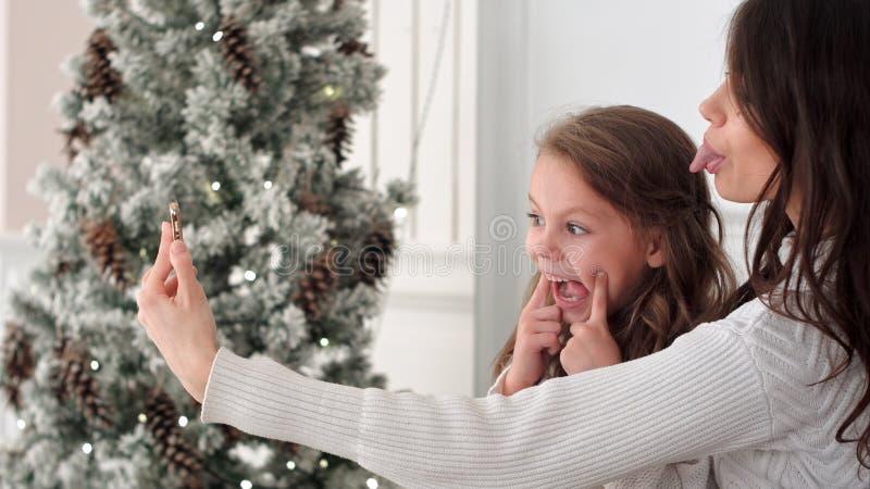 Madre feliz e hija que toman selfies divertidos de la Navidad en casa imagen de archivo libre de regalías