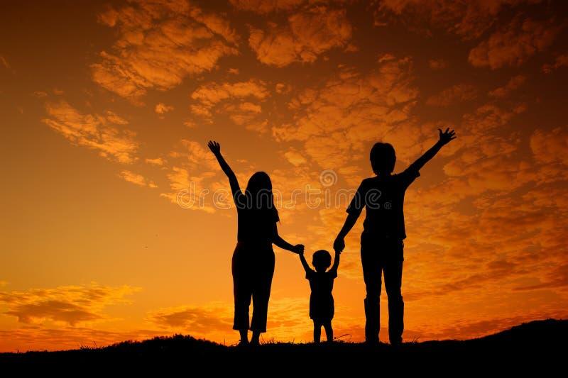 Madre feliz e hijo del padre de la familia que juegan al aire libre en la puesta del sol si imagenes de archivo