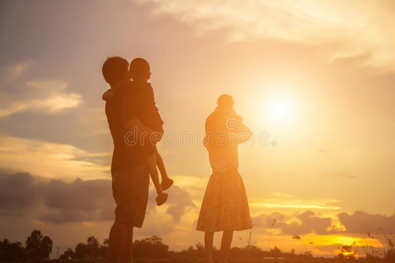 Madre feliz e hijo del padre de la familia que juegan al aire libre en la puesta del sol imagenes de archivo