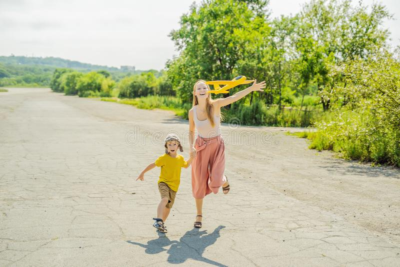 Madre feliz e hijo que juegan con el aeroplano del juguete contra viejo fondo de la pista El viajar con concepto de los niños imagenes de archivo