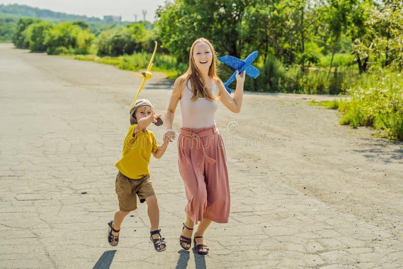 Madre feliz e hijo que juegan con el aeroplano del juguete contra viejo fondo de la pista El viajar con concepto de los niños imagen de archivo