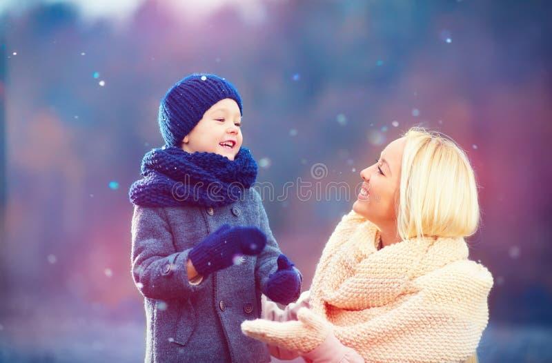 Madre feliz e hijo que juegan junto debajo de nieve del invierno fotos de archivo
