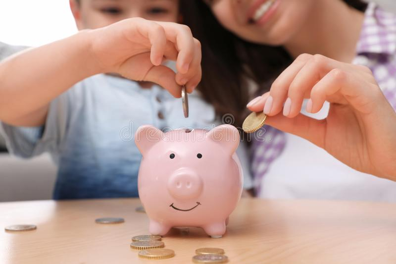 Madre feliz e hijo que ponen monedas en la hucha en casa foto de archivo libre de regalías