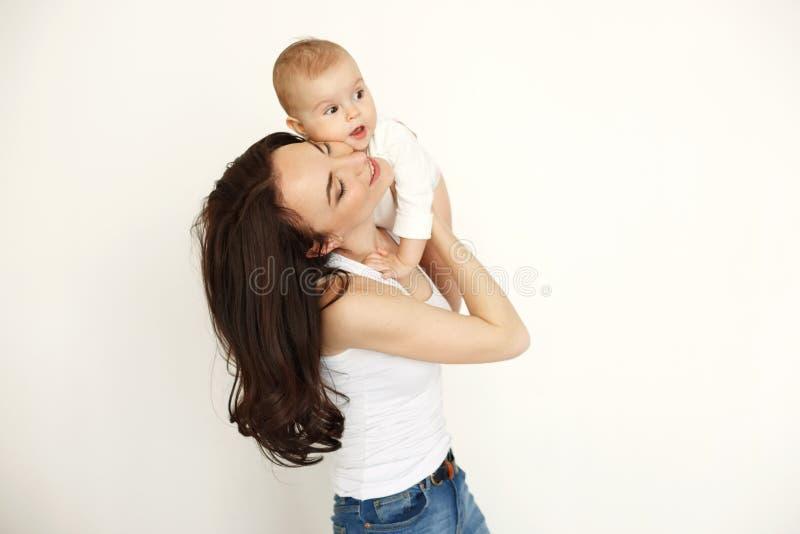 Madre feliz hermosa joven que sonríe con los ojos cerrados que detienen a su hija del bebé sobre la pared blanca imagen de archivo libre de regalías