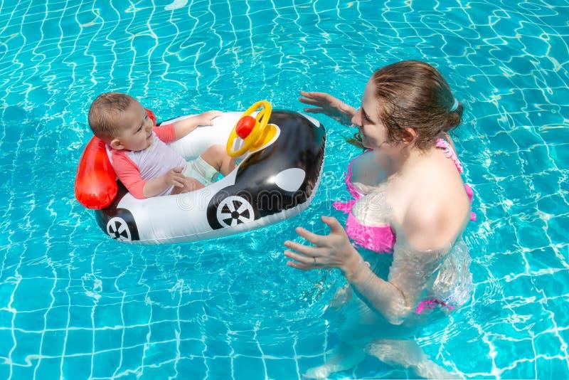 Madre feliz joven en un bikini rosado que tiene la diversión y el bebé de la captura en la piscina Un pequeño niño alegre se sien imágenes de archivo libres de regalías