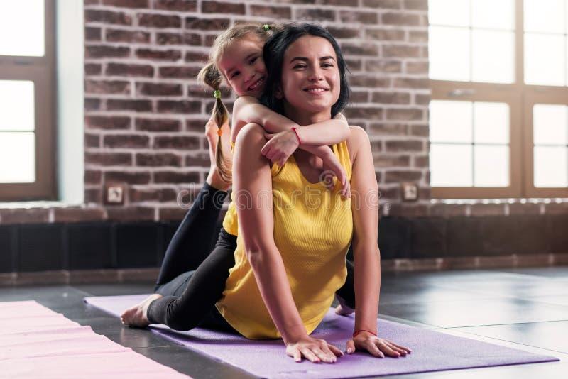 Madre feliz joven que hace estirando ejercicio en la estera mientras que su hija sonriente que la abraza en club de deportes imagen de archivo
