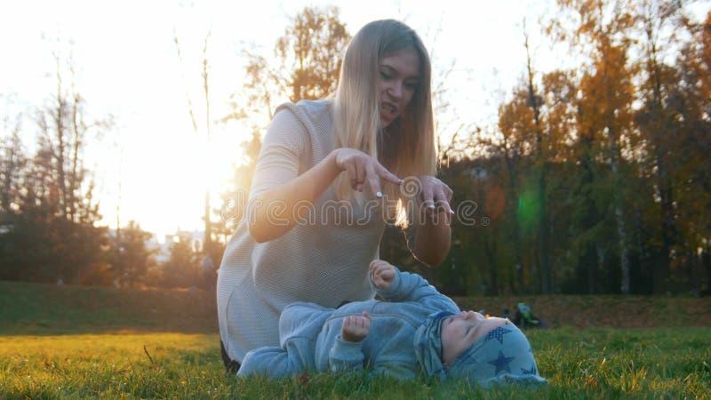 Madre feliz joven y su pequeño bebé que juegan en parque El bebé que miente en la hierba imagen de archivo libre de regalías