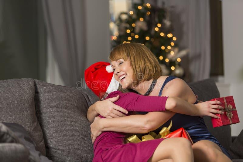 Madre feliz que abraza a la muchacha durante la Navidad en casa foto de archivo
