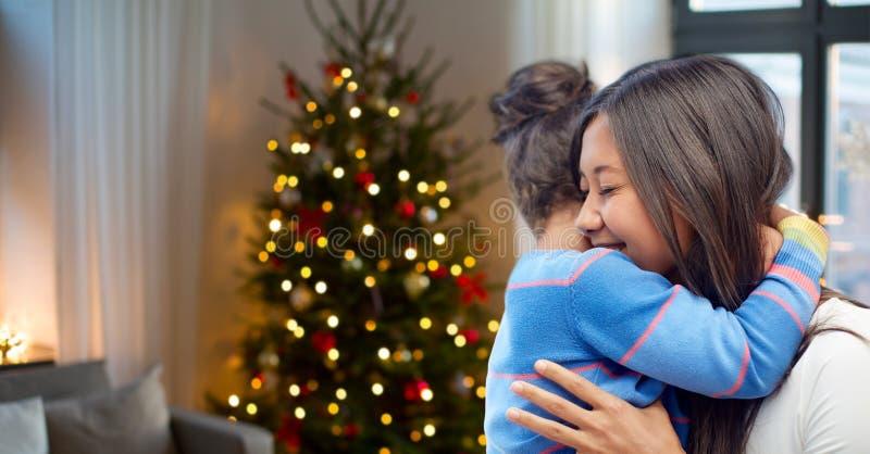 Madre feliz que abraza a su hija en la Navidad imagen de archivo