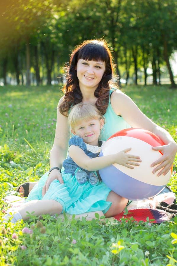 Madre feliz que abraza a su hija en naturaleza imagenes de archivo