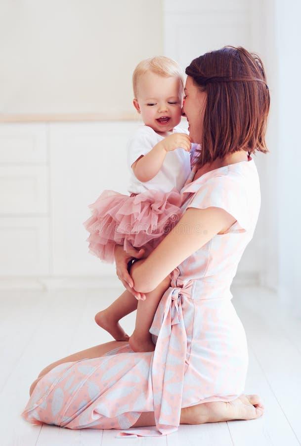Madre feliz que abraza a su pequeño bebé en casa imagenes de archivo