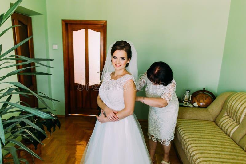 Madre feliz que ayuda a la novia que se viste para arriba en la habitación antes de ceremonia de boda imagen de archivo