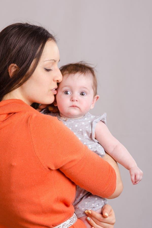 Madre feliz que besa a su hija fotos de archivo libres de regalías