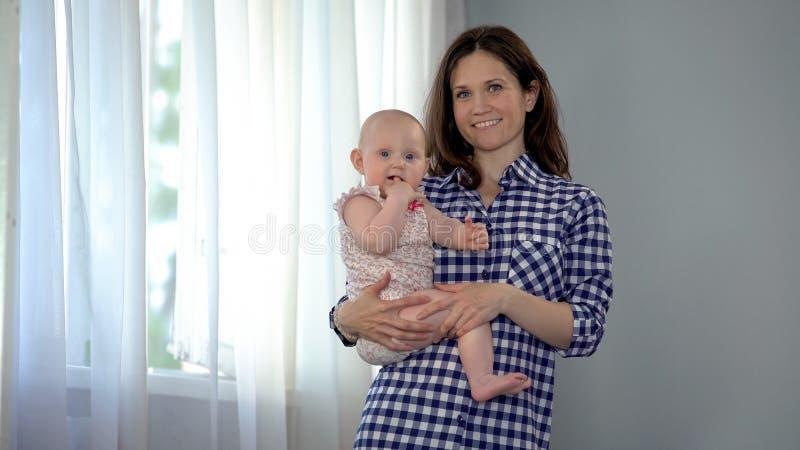 Madre feliz que celebra al bebé lindo en los brazos, sonriendo en cámara, maternidad foto de archivo