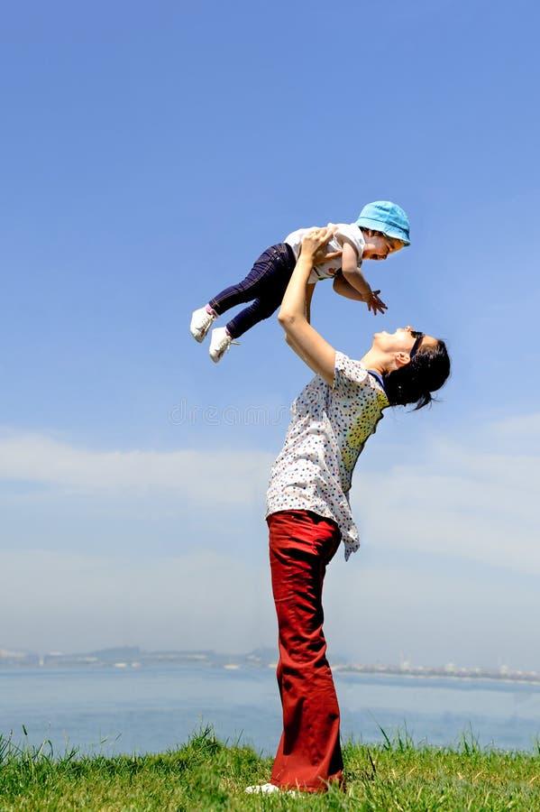 Madre feliz que coge a su bebé al cielo en el SP imágenes de archivo libres de regalías