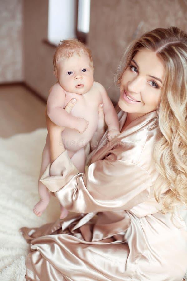 Madre feliz que juega con el bebé que se sienta en cama Mamá que abraza su d imagenes de archivo