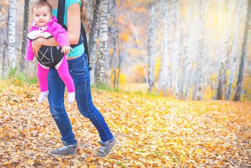 Madre feliz que lleva a su niño por el portador de bebé ergonómico imagen de archivo libre de regalías