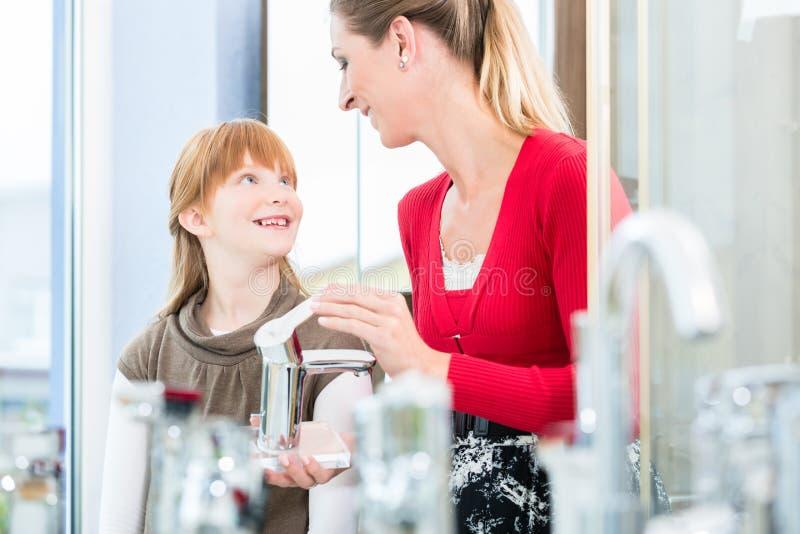 Madre feliz que mira con su hija dos grifos en una tienda sanitaria de las mercancías imágenes de archivo libres de regalías