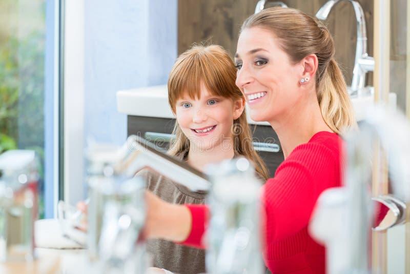 Madre feliz que mira con su hija dos grifos en una tienda sanitaria de las mercancías foto de archivo libre de regalías
