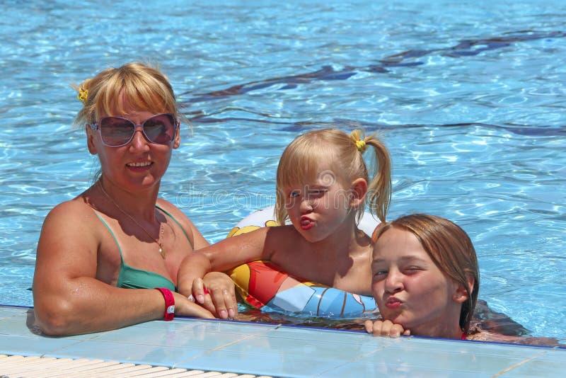 Madre feliz que se divierte que salta con sus hijas en hierba verde Equipo feliz de la familia Familia que disfruta de vacaciones imagenes de archivo