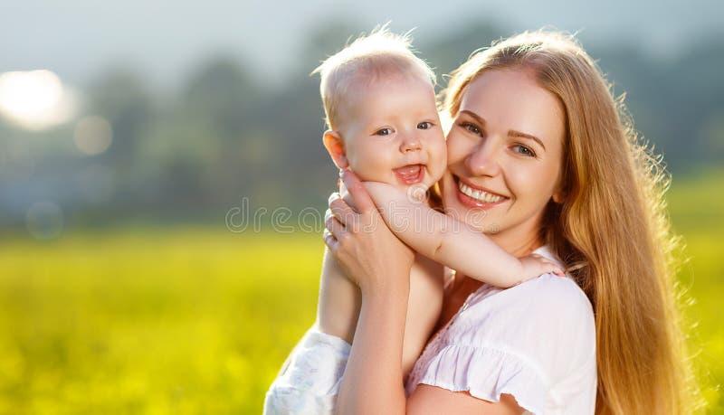 Madre feliz y bebé de la familia que abrazan la naturaleza en verano fotografía de archivo