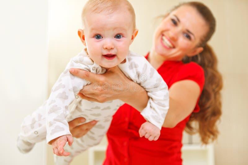 Madre feliz y bebé encantador que juegan en el diván fotografía de archivo libre de regalías