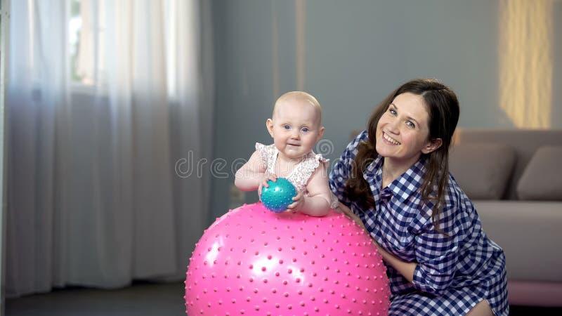 Madre feliz y bebé lindo que sonríen en la cámara, jugando con las bolas en casa fotos de archivo