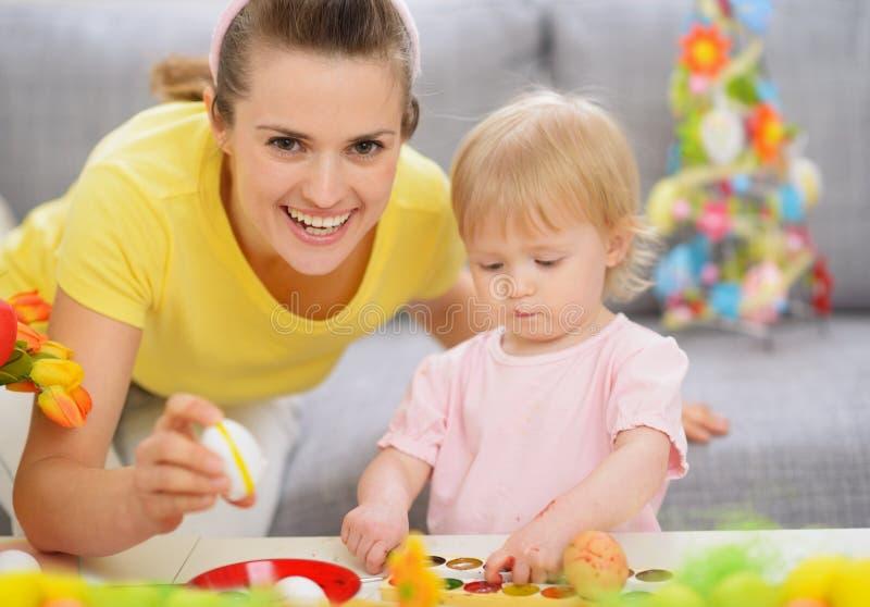 Madre feliz y bebé que hacen las decoraciones de Pascua fotos de archivo libres de regalías