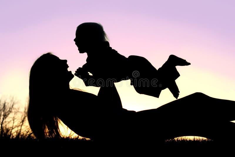 Madre feliz y bebé que juegan la silueta exterior imagen de archivo libre de regalías