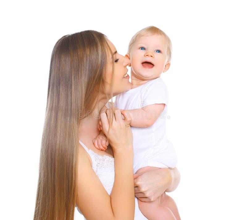 Madre feliz y bebé sonrientes que juegan en blanco foto de archivo