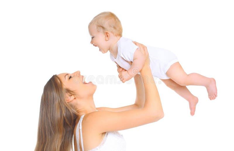 Madre feliz y bebé sonrientes que juegan en el fondo blanco foto de archivo