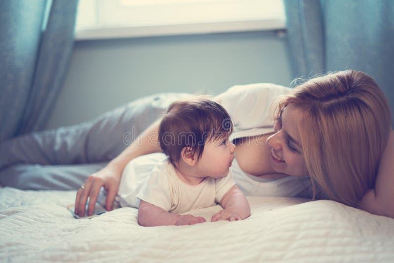 Madre feliz y bebé sonrientes que mienten en cama en casa imagen de archivo libre de regalías