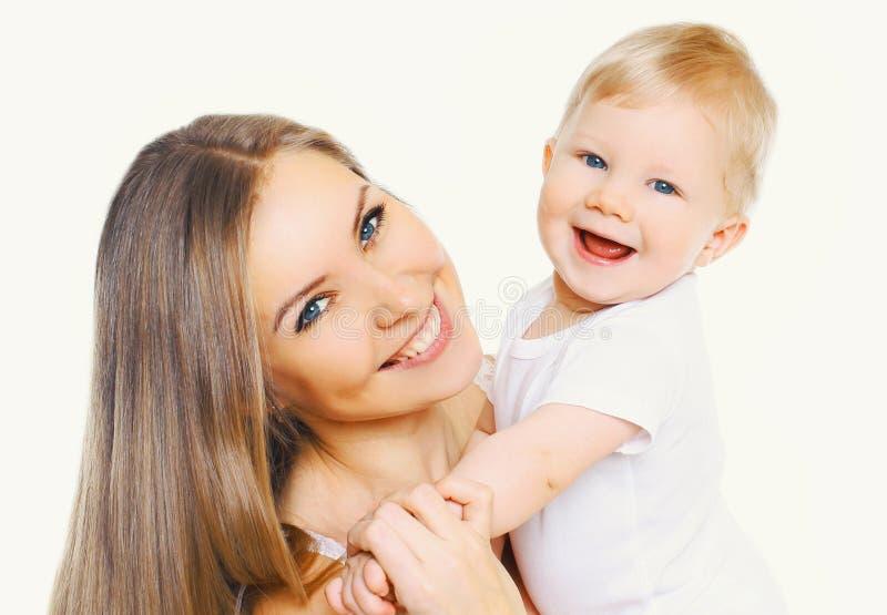 Madre feliz y beb? sonrientes del primer del retrato que se divierten junto aislada en blanco foto de archivo