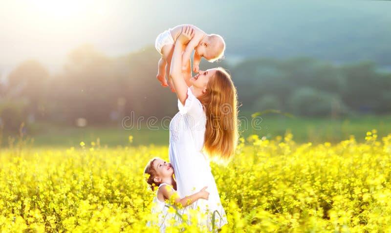 Madre feliz y childrn de la familia que abrazan la naturaleza en verano fotografía de archivo