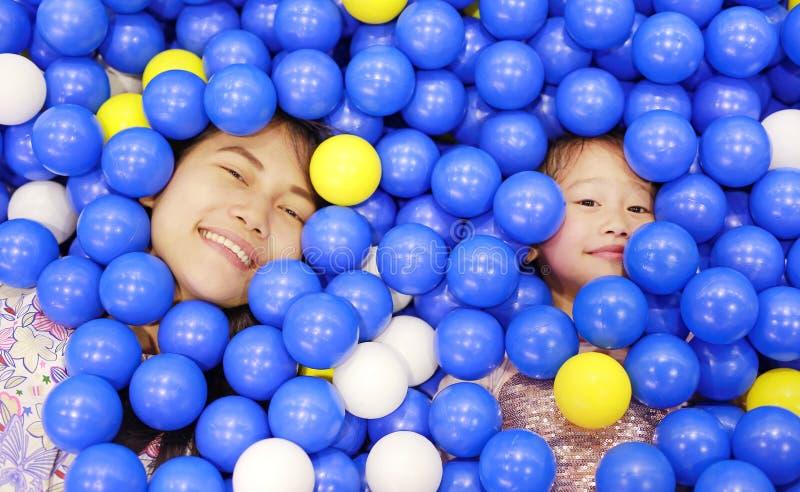 Madre feliz y niña que juegan con el patio plástico de las bolas del color fotos de archivo libres de regalías
