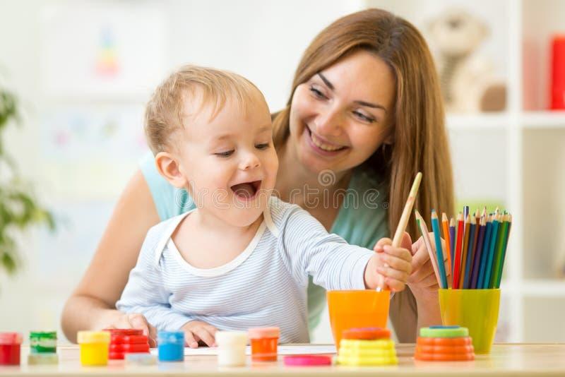 Madre feliz y niño de la familia que pintan junto imagen de archivo