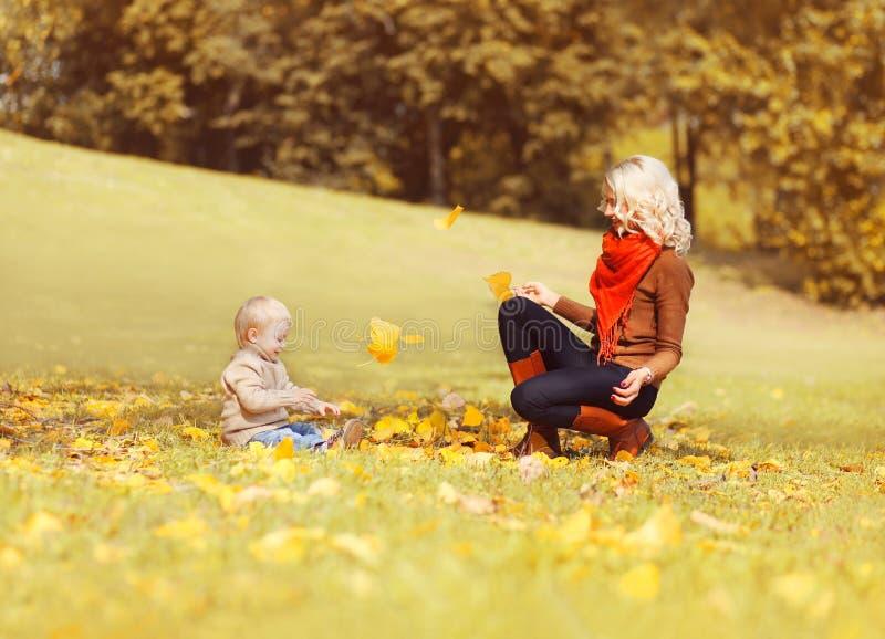 Madre feliz y niño que juegan así como las hojas amarillas en la hierba que se divierte en parque del otoño foto de archivo libre de regalías