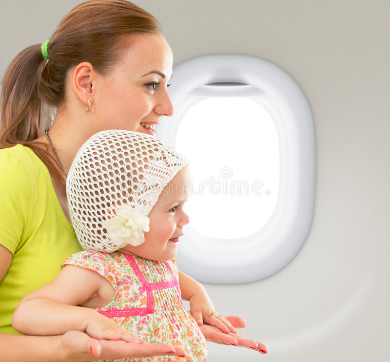 Madre feliz y niño que se sientan junto en cabina del aeroplano fotografía de archivo