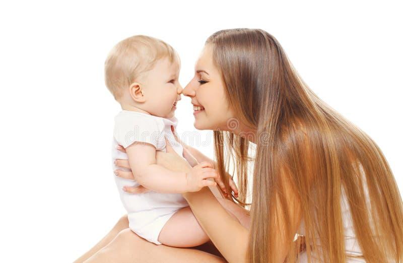 Madre feliz y niño sonrientes que juegan en el fondo blanco imagen de archivo