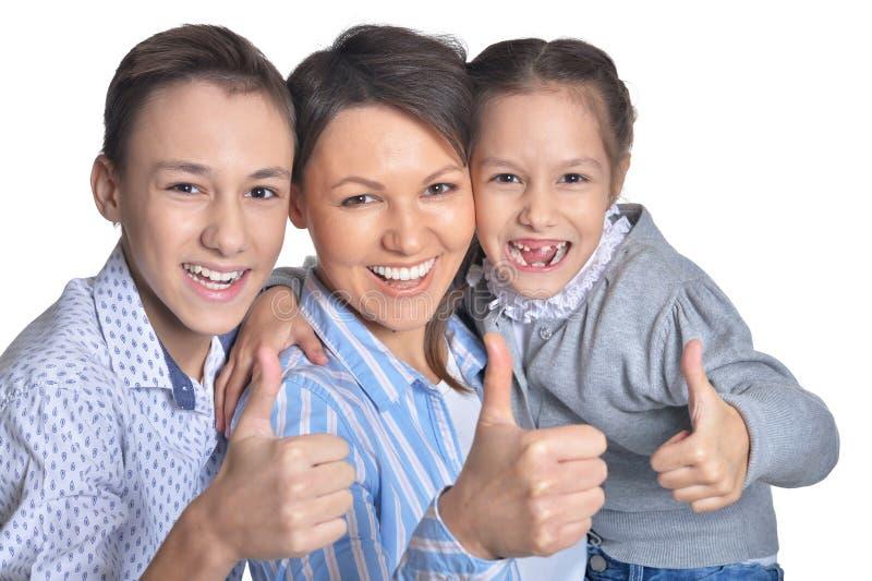 Madre feliz y ni?os sonrientes que muestran los pulgares para arriba junto en el fondo blanco fotografía de archivo libre de regalías