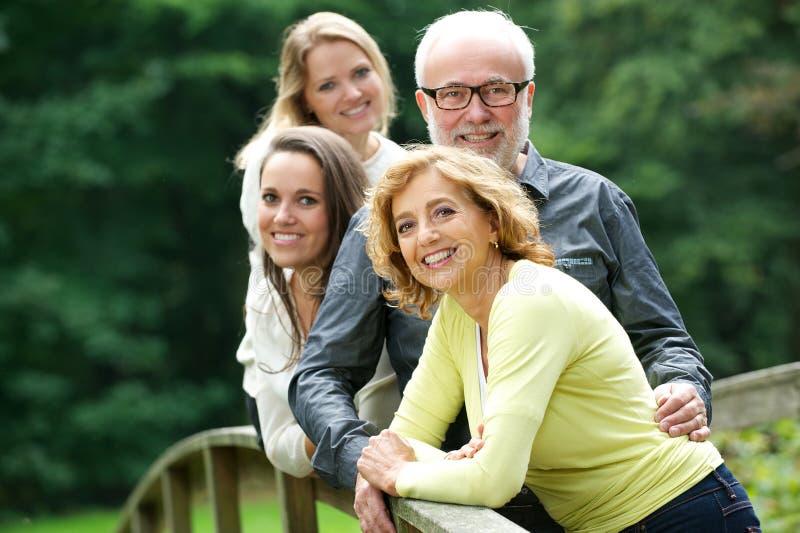 Madre feliz y padre que se colocan con dos hijas al aire libre fotos de archivo