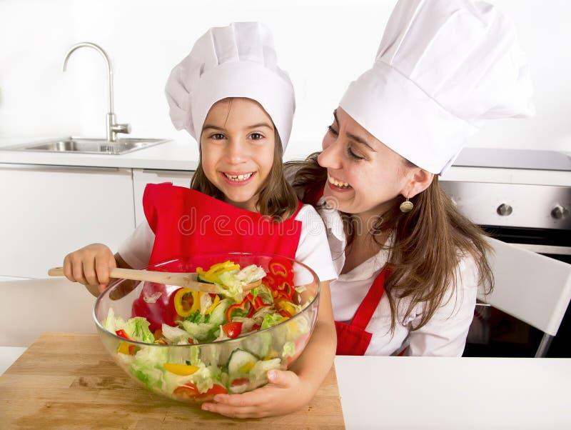 Madre feliz y pequeña cocina de la hija en casa que preparan la ensalada en sombrero del delantal y del cocinero fotos de archivo libres de regalías