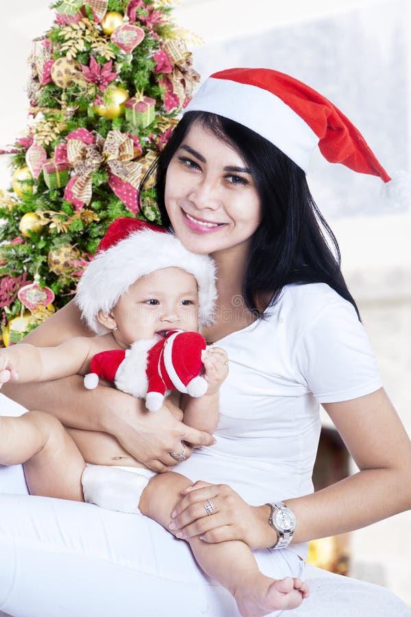 Madre feliz y su bebé en el sombrero de Santa Claus fotografía de archivo