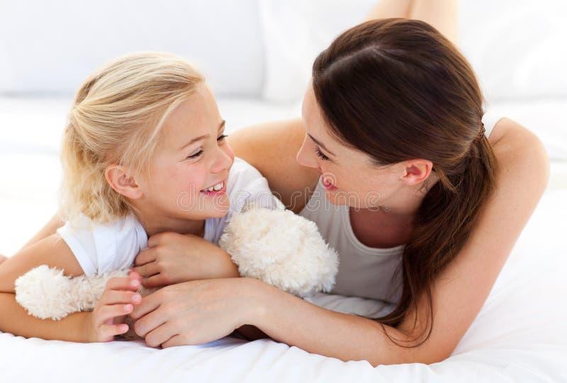 Madre feliz y su hija que juegan junto imagenes de archivo