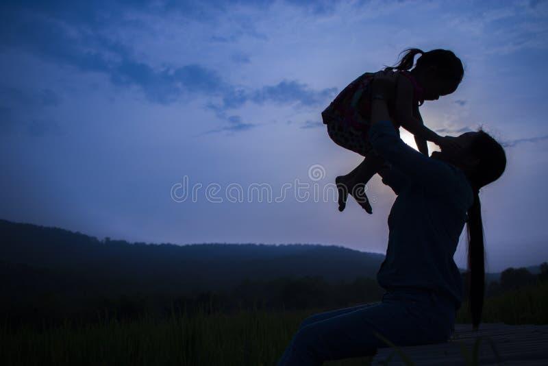 Madre feliz y su juego de ni?os al aire libre que se divierten, hija de elevaci?n de la madre en campo del arroz imagenes de archivo