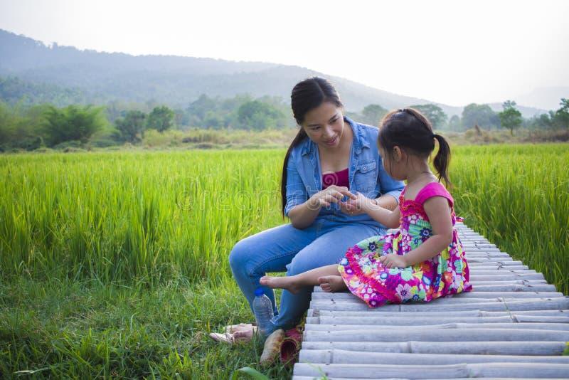 Madre feliz y su juego de ni?os al aire libre que se divierten, tierra trasera del campo verde del arroz imágenes de archivo libres de regalías