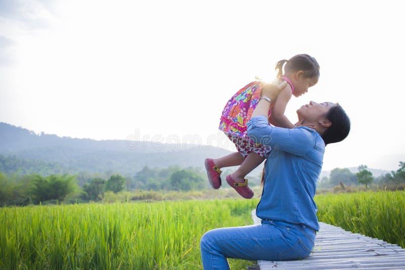 Madre feliz y su juego de ni?os al aire libre que se divierten, tierra trasera del campo verde del arroz imagen de archivo