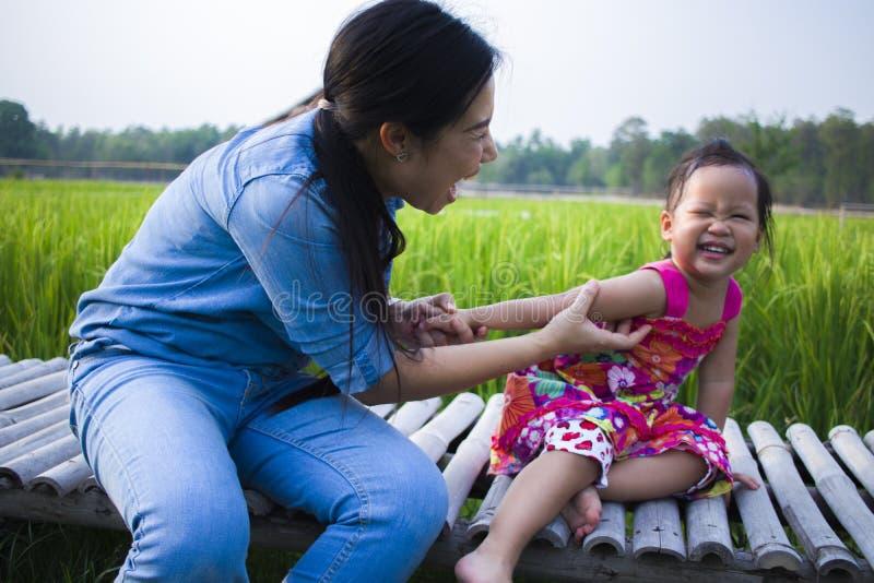 Madre feliz y su juego de ni?os al aire libre que se divierten, tierra trasera del campo verde del arroz foto de archivo