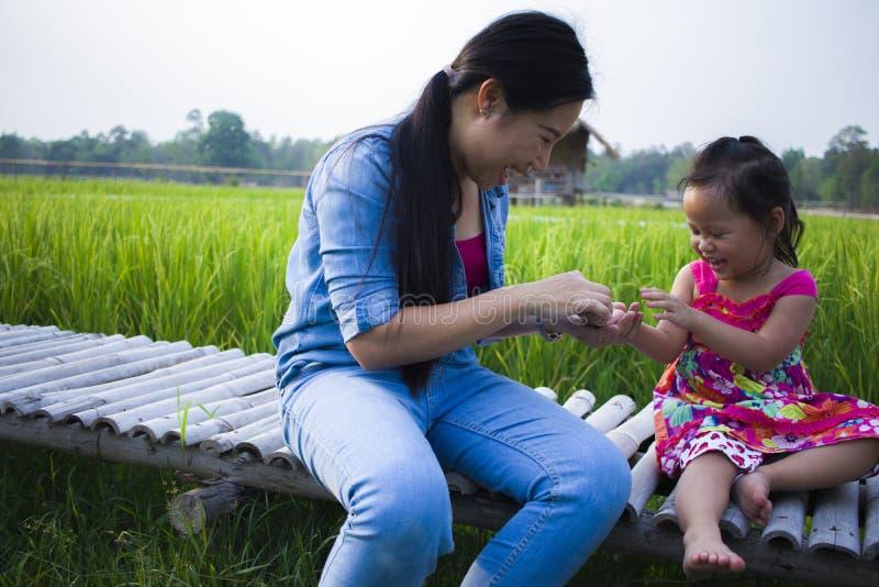 Madre feliz y su juego de ni?os al aire libre que se divierten, tierra trasera del campo verde del arroz foto de archivo libre de regalías