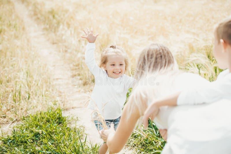 Madre feliz y sus niños que pasan el tiempo junto en campo soleado fotografía de archivo libre de regalías